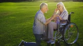 cadeira de rodas : Senior man on knee proposing woman on wheelchair Stock Footage