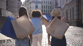 Back view of women putting paper bags on shoulder