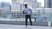 паз : Active black male dancing afrobeat style in city