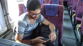 Young man with beard in summer clothes uses his smartphone while sitting in a travel coach