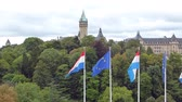 Luxembourg and EU Flag waving in historic centre of Luxembourg, in the background the tower of Luxembourg city