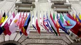 ,International flags from OSCE and several nations waving in the wind in front of a historical building Vídeos