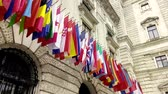 viyana : ,International flags from OSCE and several nations waving in the wind in front of a historical building Stok Video