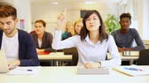 happy : Smiling asian student raising her hand in a classroom (Full HD) Stock Footage