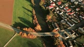 Aerial pan shot of village with river and bridge