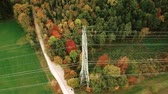 Aerial tracking shot of overhead power line among autumn forest landscape