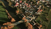 Aerial pan shot of country road running through German village in fall