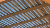 veranda : A wooden canopy against a clear sky background on a sunny day. Geometry in space, intersecting lines. Shades of yellow on a blue background Stok Video