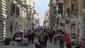 Valletta, Malta – February 17, 2017: Local Maltese people and tourists walking on Republic Street. This street is located at the heart of the city and very popular location for shopping and cultural activities. Vídeos