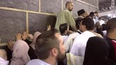 Mecca, Saudi Arabia - September 7, 2016: Muslim men and female believers touching the wall of Kaaba during Hajj in Saudi Arabia