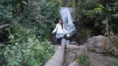 Asian girl walking on a fallen tree near waterfall.