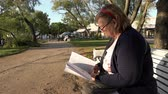 starość : pensioner carefully reads books on a park bench in the sunny season