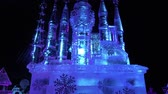 esculpir : Russia, Saint-Petersburg, December 27, 2015 Fairy princess castle of clear blue ice as an exhibition exhibit shimmers in the rays of bright colors