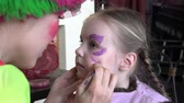 paint : professional makeup and manicure vegetable dyes specialist performs pattern on a childs face in the form of butterflies Stock Footage