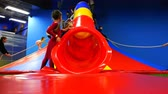 kidzania : Children roll down the steep descent of the red hill to soft mats