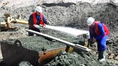 trough : Two workers at the quarry sort the raw materials in an iron trough