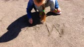 hand written : the girl squatting writes on the sand the word mom Stock Footage