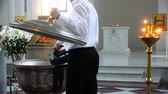 chrzest : a church employee pours holy water into a font for babies.