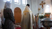 ortodoksluk : Father in a cassock recites a prayer at the baptism of a baby Stok Video