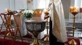 chrzest : the priest lights the burning candle with water in the font for the ritual of baptism.