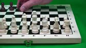 peones : the opponent places a number of black figures on a chessboard. Archivo de Video