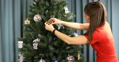 sněhulák : Housewife hangs blue glass garland on the Christmas tree