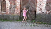 knocking : girl with delight peeks into the closed wooden doors.