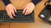 press up : fingers typing on the black keyboard in the office near the phone. Stock Footage