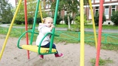 gündelik : The child is swinging on the swings in the summer.