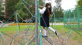 작업장 : The school-girl in the uniform is climbing on the rope slide.