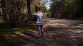 babies : Little girl walks on a forest road in summer Stock Footage