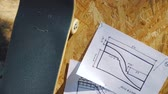 embarque : view of a new skateboard on a wooden background with plans for a miniramp in a skatepark in the summer