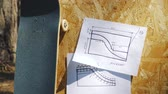 rampa : view of a new skateboard on a wooden background with plans for a miniramp in a skatepark in the summer