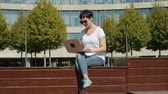 korespondence : young business woman in a white T-shirt sitting in front of an office building and working on a computer