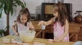 magdalenas : two little girls put cream on the molds to make cupcakes