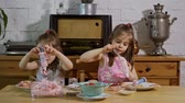 çörek : two little girls put on a cream and decorate delicious cupcakes on a wooden table