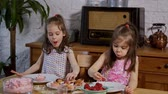 magdalenas : two little girls put on a cream and decorate delicious cupcakes on a wooden table