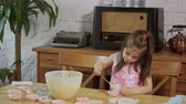 muffinki : two little girls put cream on the molds to make cupcakes