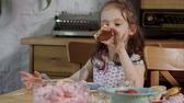 muffinki : little girl decorates and eats delicious cupcakes