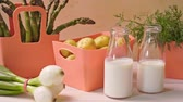 koperek : Spring young vegetables in coral containers and bottles with milk on table
