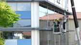 árido : Empoli, Italy - 17 May 2016: Window cleaner working on a glass facade of the building. Cleaning Maintenance of USL 11 in Gods street Capuchins in Empoli.