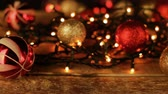 Christmas decoration with balls and lights on wooden table.