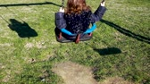 tření : Toddler girl plays on the swing. Science concept, example of shadow, energy, inertia and gravity. Dostupné videozáznamy
