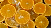gele achtergrond : Water pouring to orange fruit slow motion