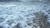 çakıl : Close up of foam formed by waves breaking on a seashore with many small stone on the beach. Stok Video