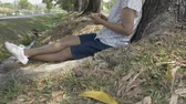 relaxar : Asian woman in casual dress sitting under the tree and using mobile phone with social online in public park.