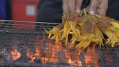 Grilled squids on a charcoal grill with a mans hands rotating the skewers. Local street food in thailand.