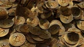 Close up shot of large amount of Bitcoins falling over a table