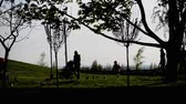 People walking in a park with children, silhouettes, forest park, sunset behind trees, outdoors, autumn, summer, spring