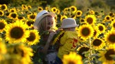 Beautiful mother is tossing up her cute little son in sunflower field. Both are happy. Image with selective focus Wideo